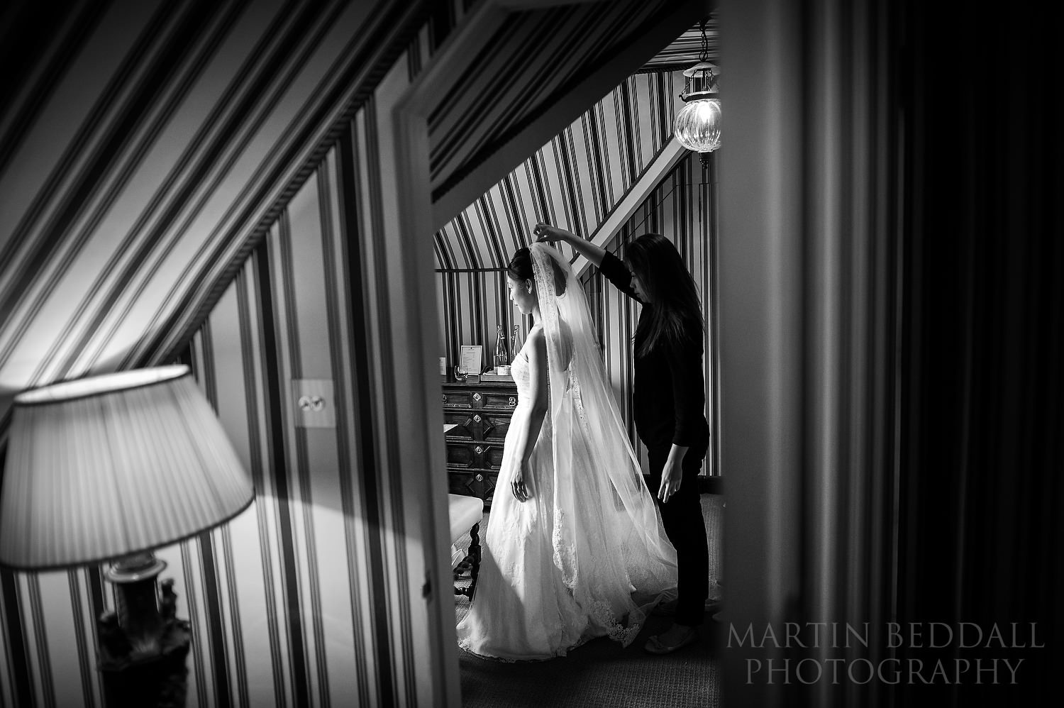Bride gets into her wedding dress at Great Fosters