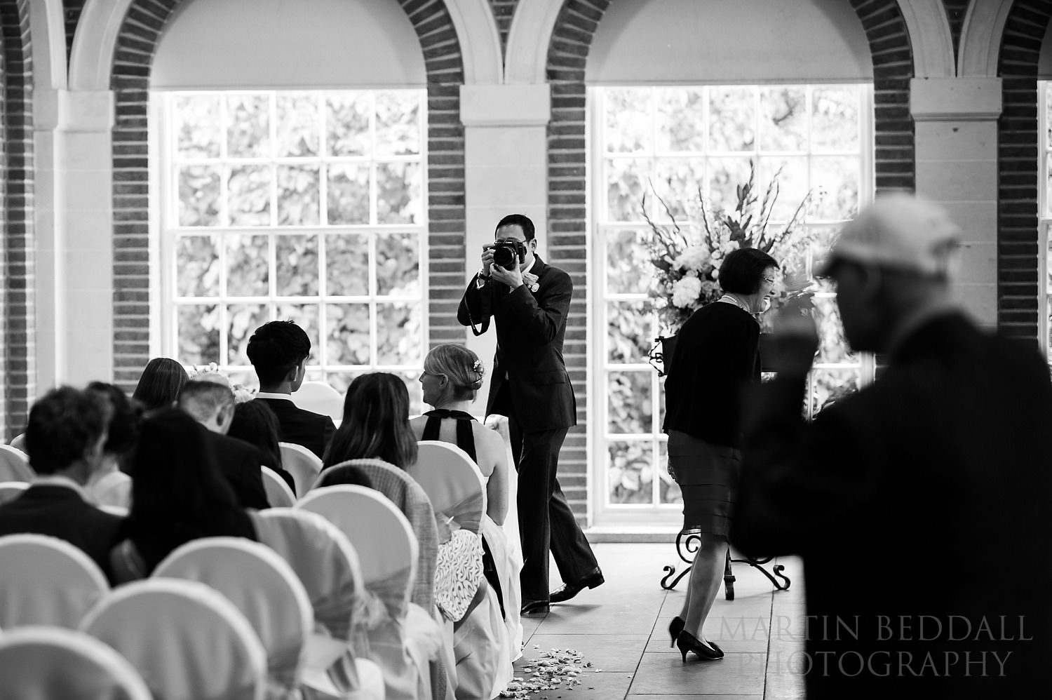 Groom with his own camera in the ceremony room at Great Fosters