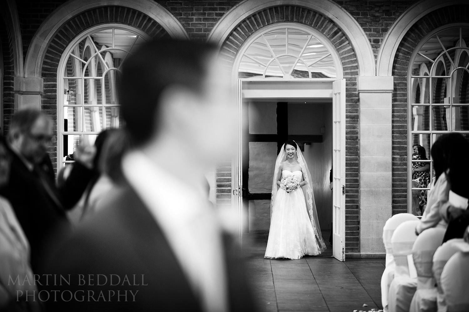 Bride enters the ceremony room at Great Fosters