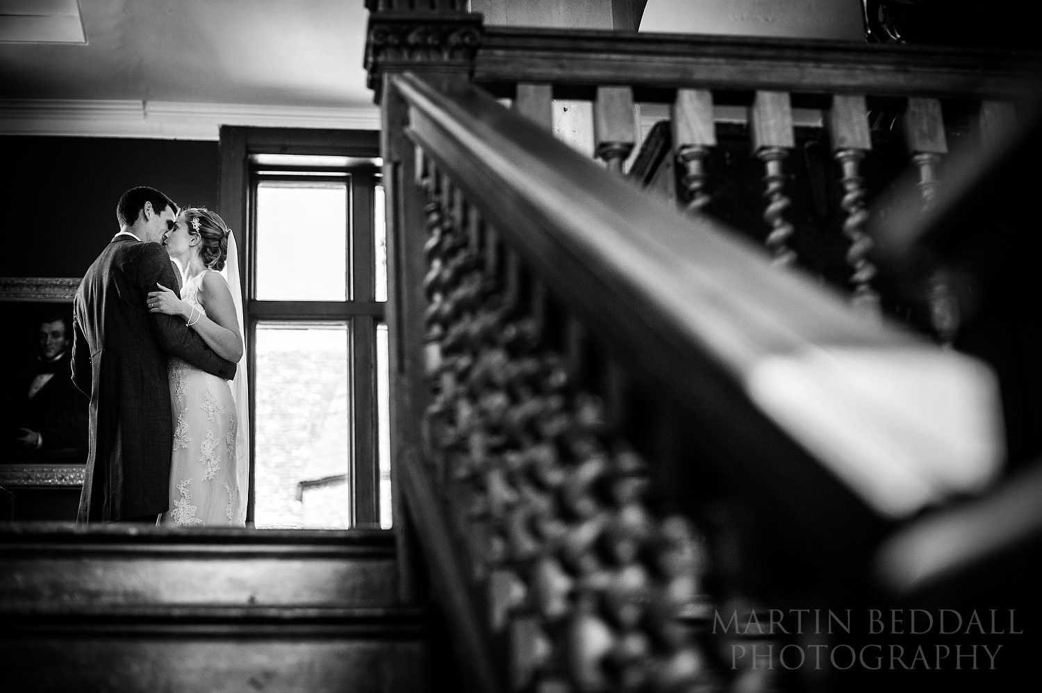 Bride and groom kiss at the top of the stairs
