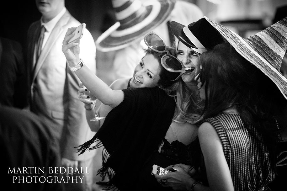Glamourous wedding guests take a selfie of themselves during the wedding reception
