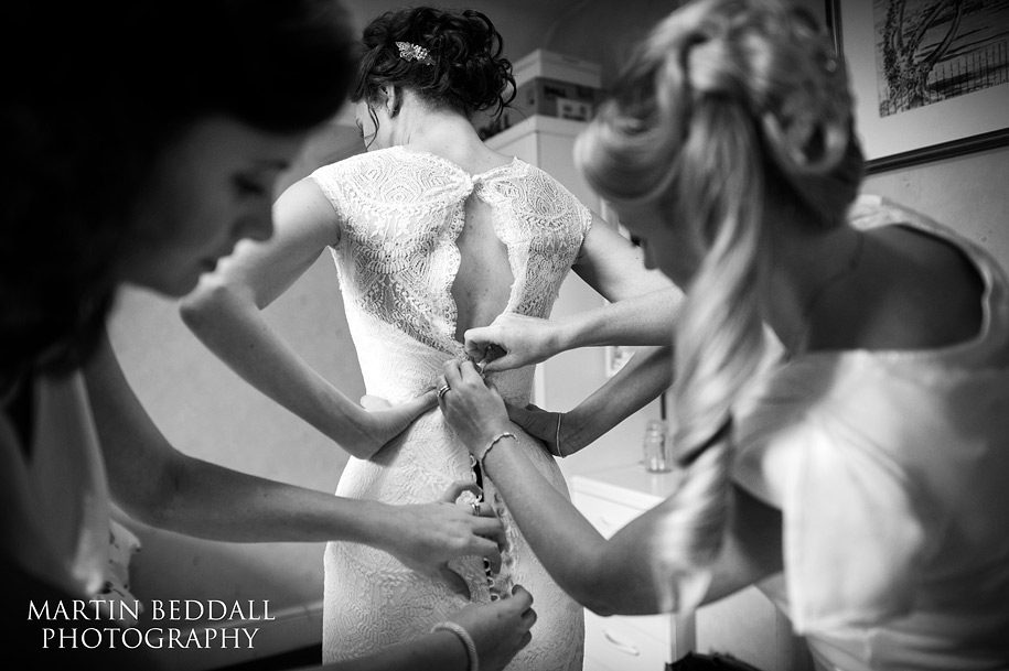 Bride has her wedding dress done up by bridesmaids