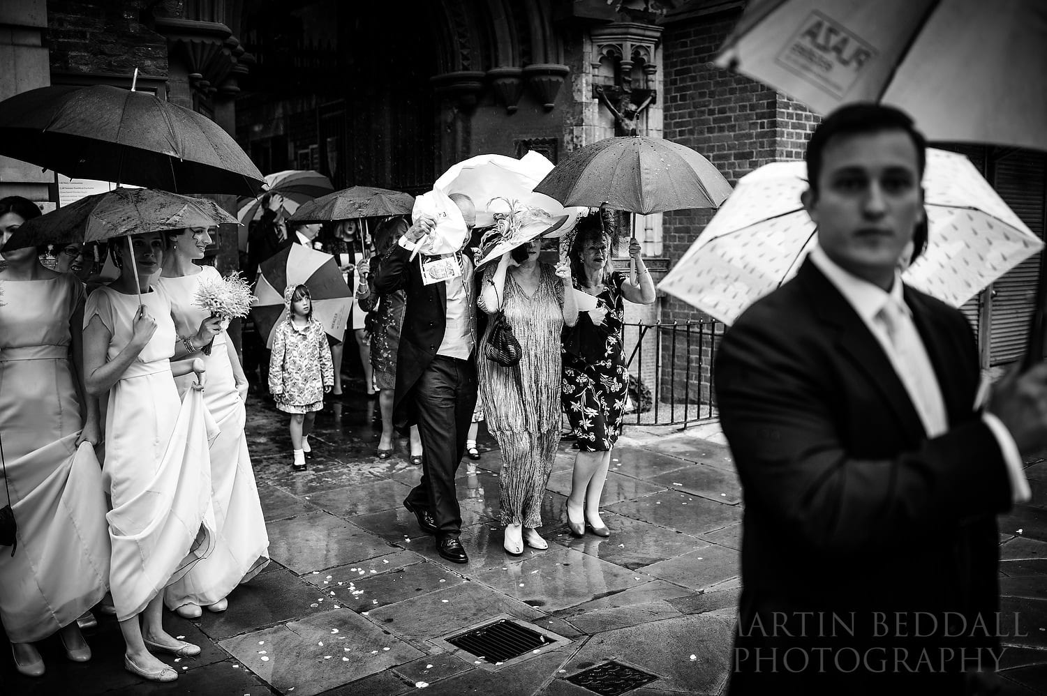 Downpour a sguests leave the church at London wedding