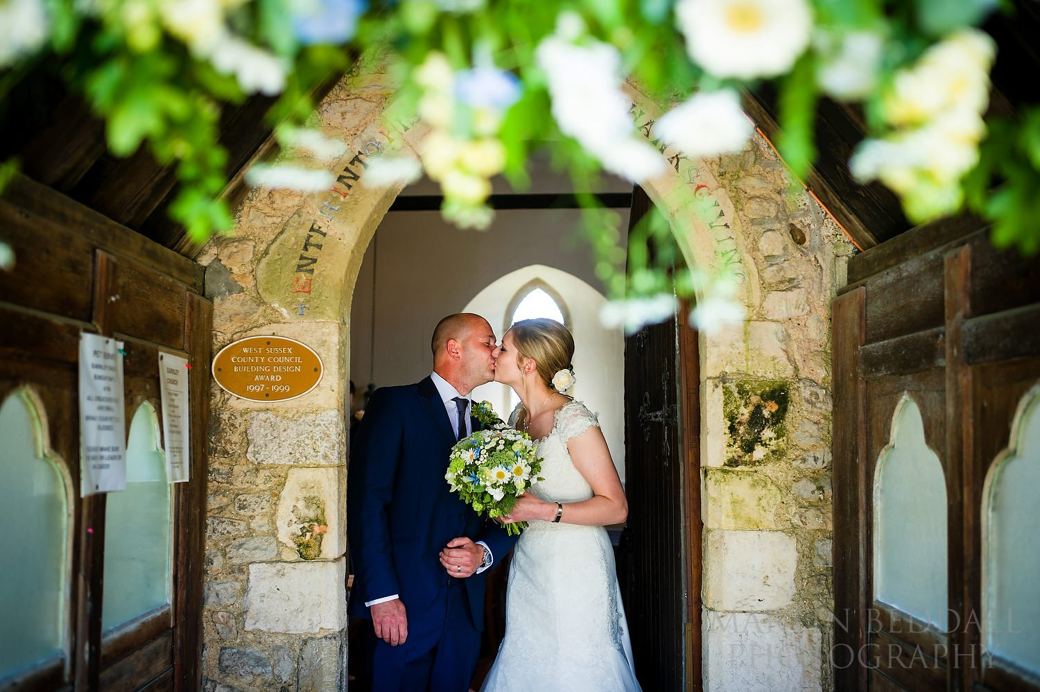 Bride and groom kiss in the porch of Earnley church in Sussex