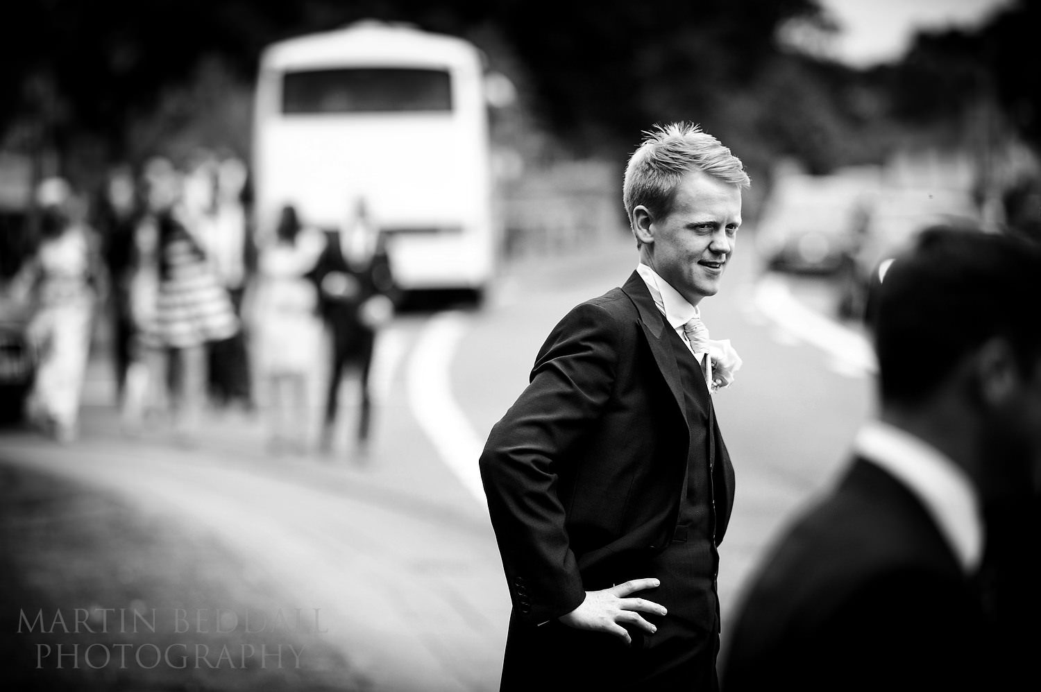 Groom outside Chiddingfold church as guests arrive by coach