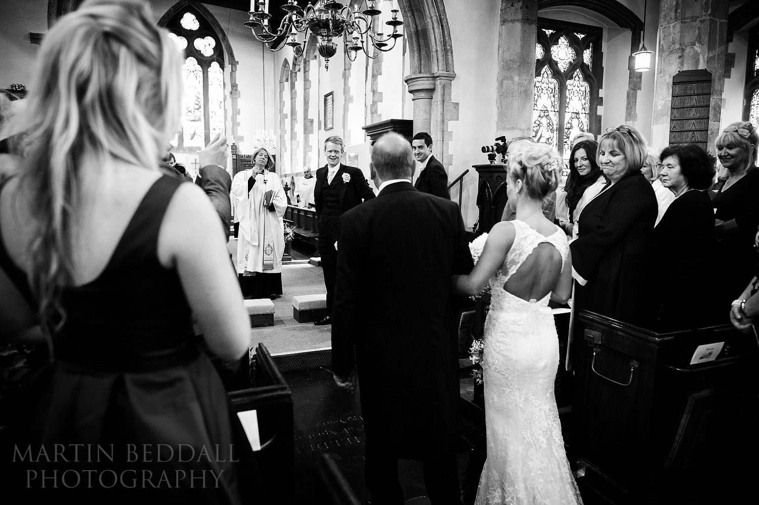 Bride walks up the aisle with her father at Chiddingfold church
