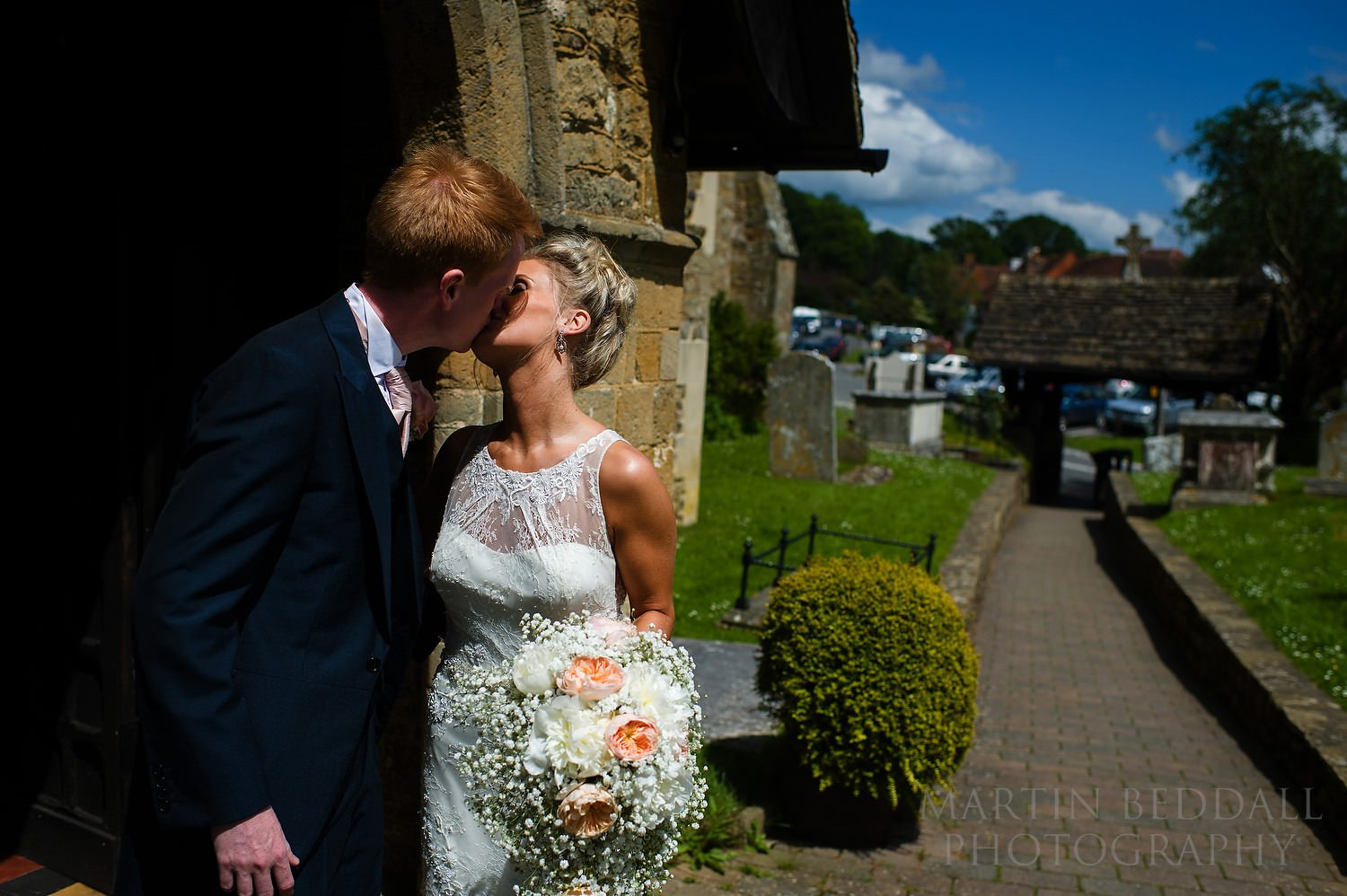 Bride and groom kiss outside St Marys church in Chiddingfold