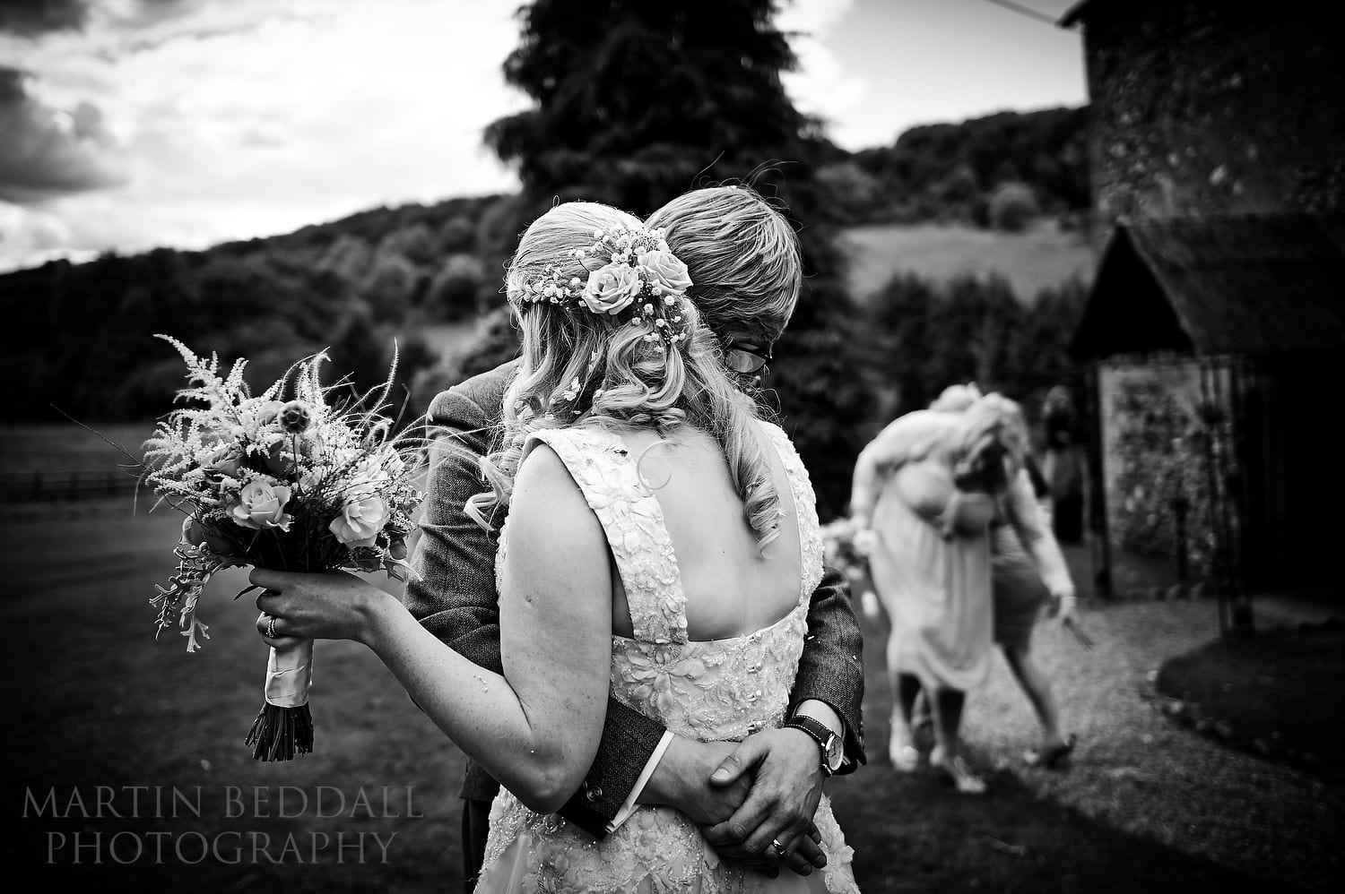 Couple embrace outside the chapel at the Lost Village of Dode wedding