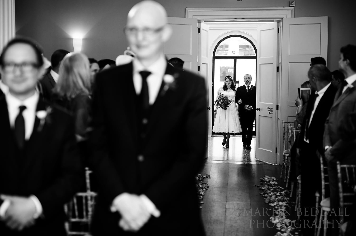 Bride enters the ceremony room at Royal Society of Arts with her father