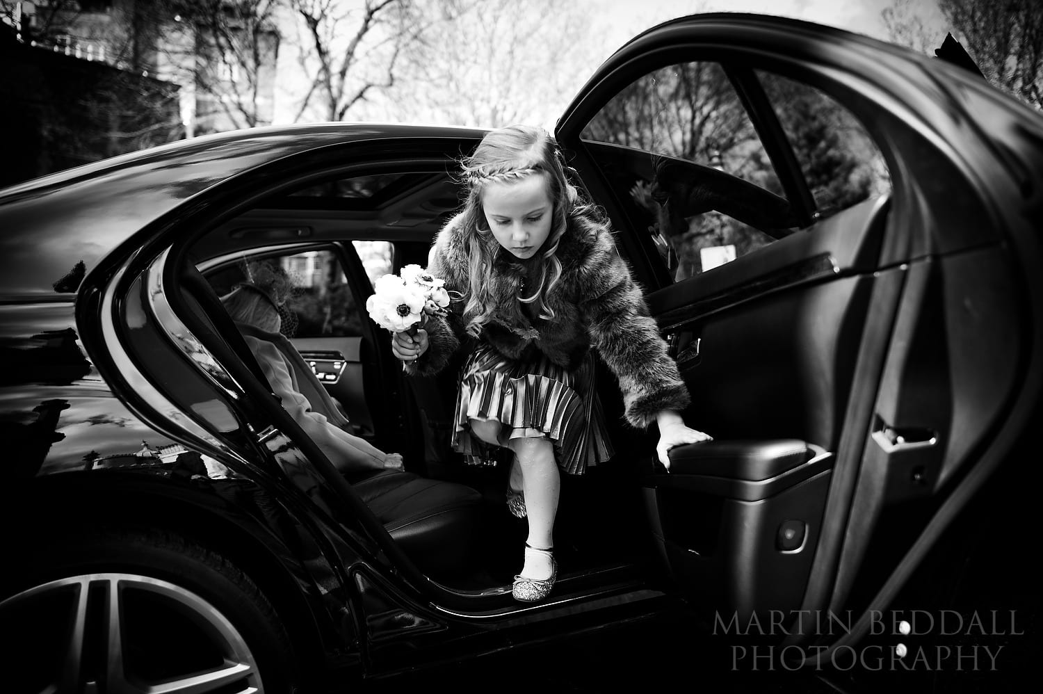 Flower girl steps out of the wedding car