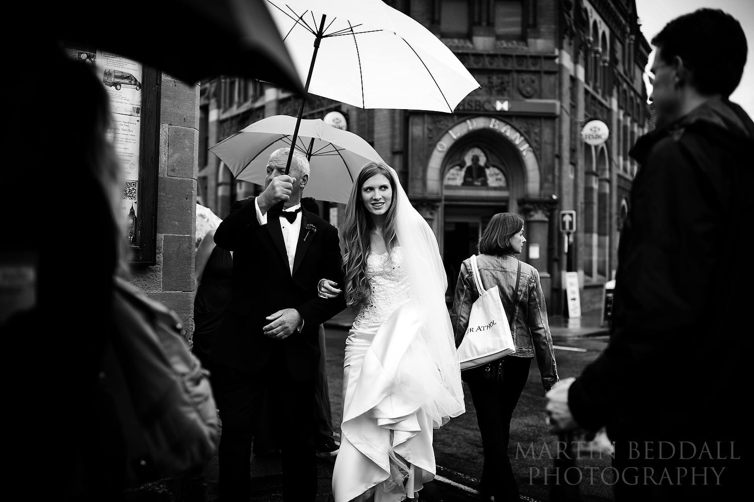 Walking to the wedding ceremony in the rain