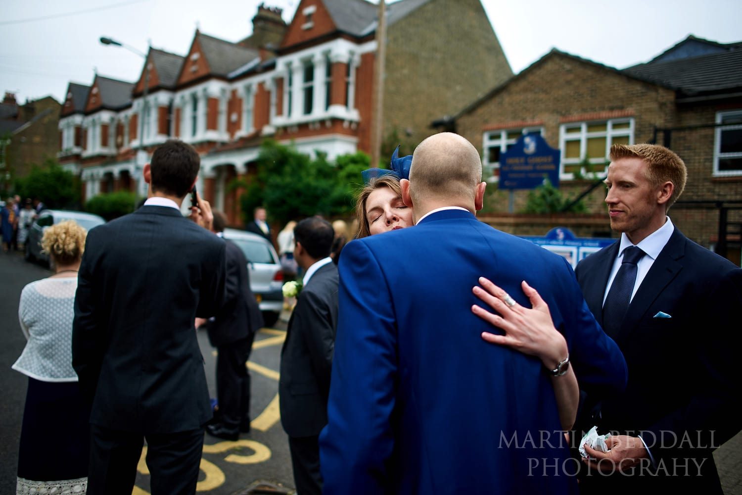 Groom greeting guests oustside the church in Balham