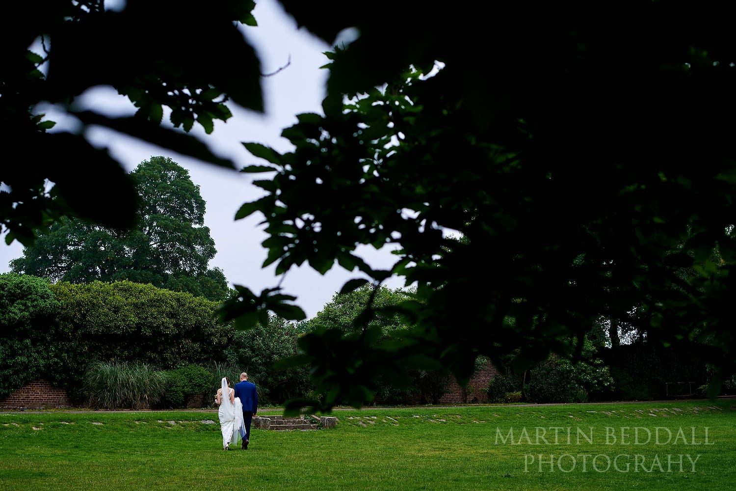 Bride and groom walk in the grounds of Hampton Court House