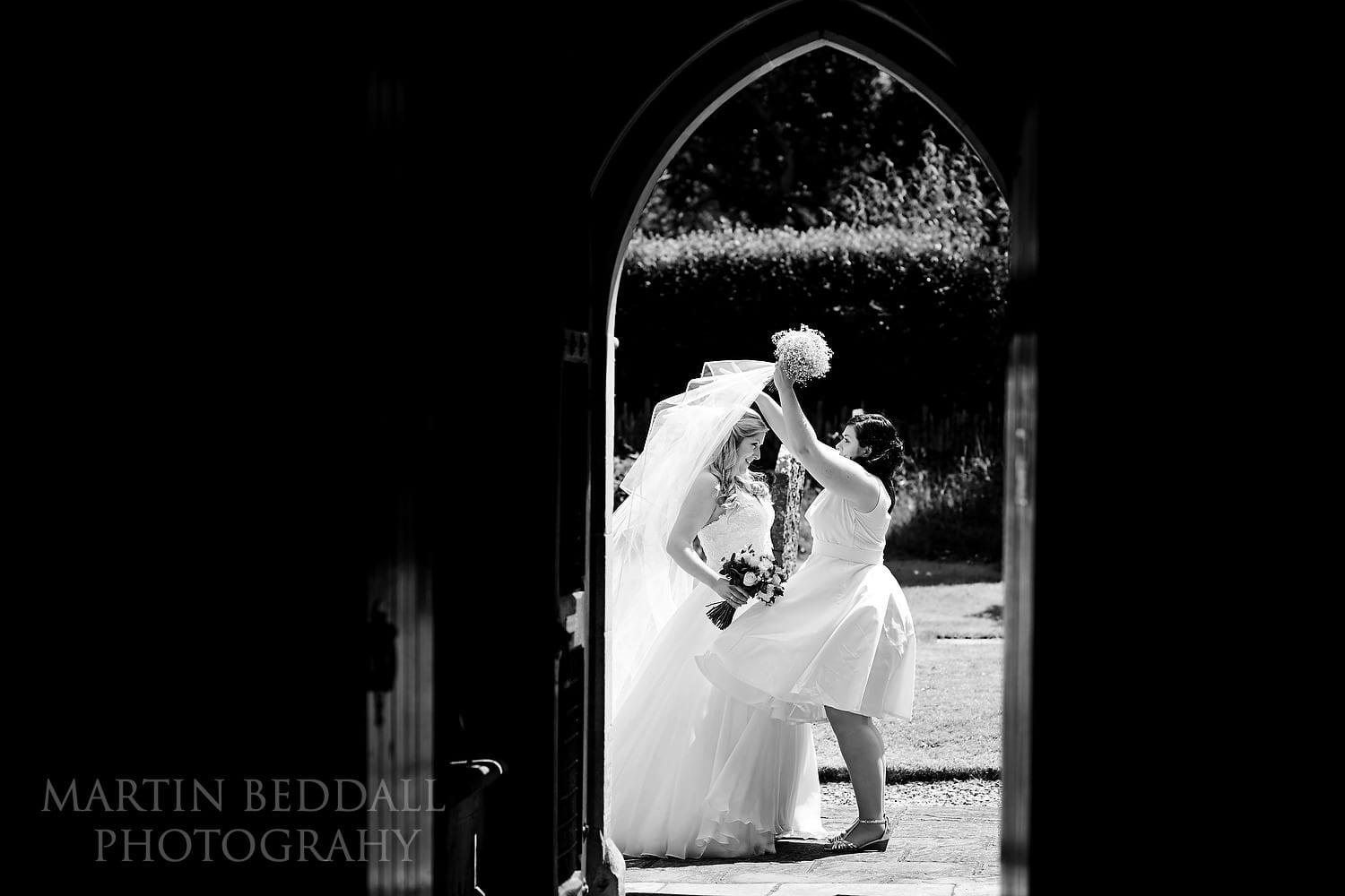 Bride's sister helps fix her veil in the wind