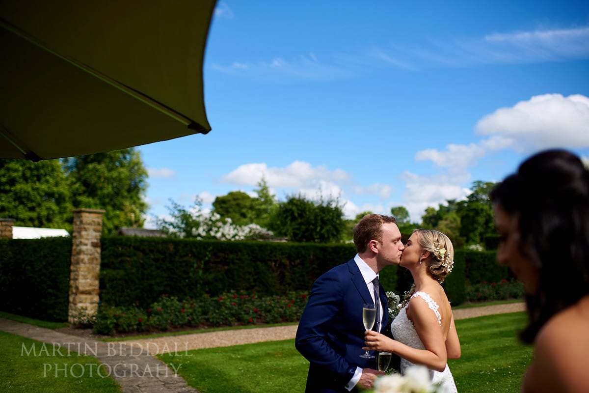 Bride and groom kiss on the lawn at Hever Castle