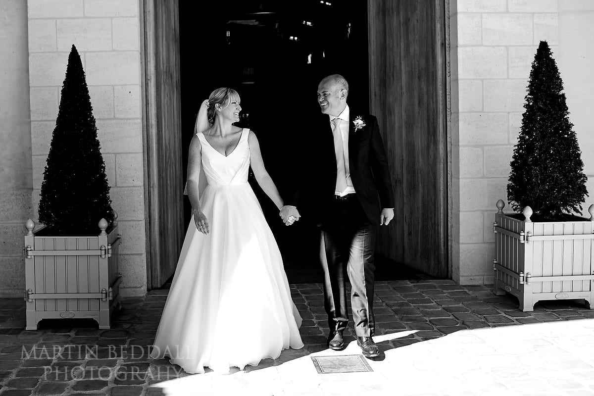 Bride and groom walk out into the sunshine at Château Soutard