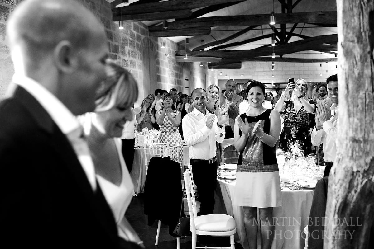 Guests applaud the bride and groom into dinner
