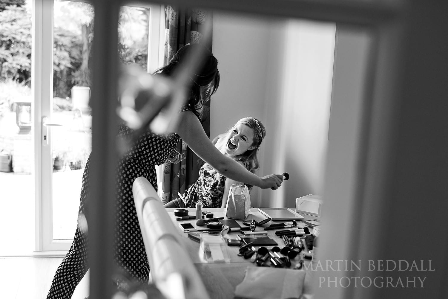 Bride laughing with friends as she gets ready