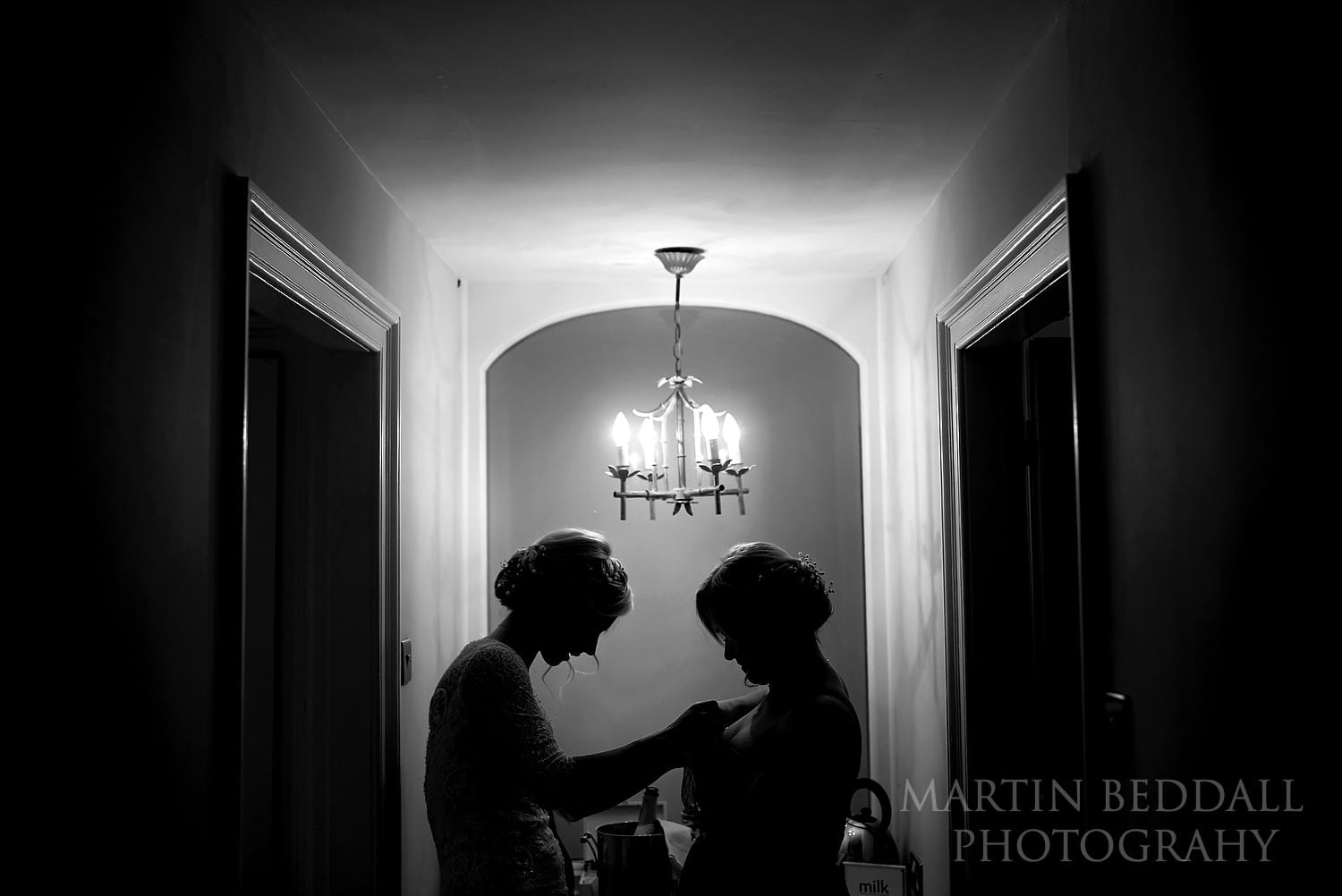 Bride helps her sister get ready at East Sussex wedding