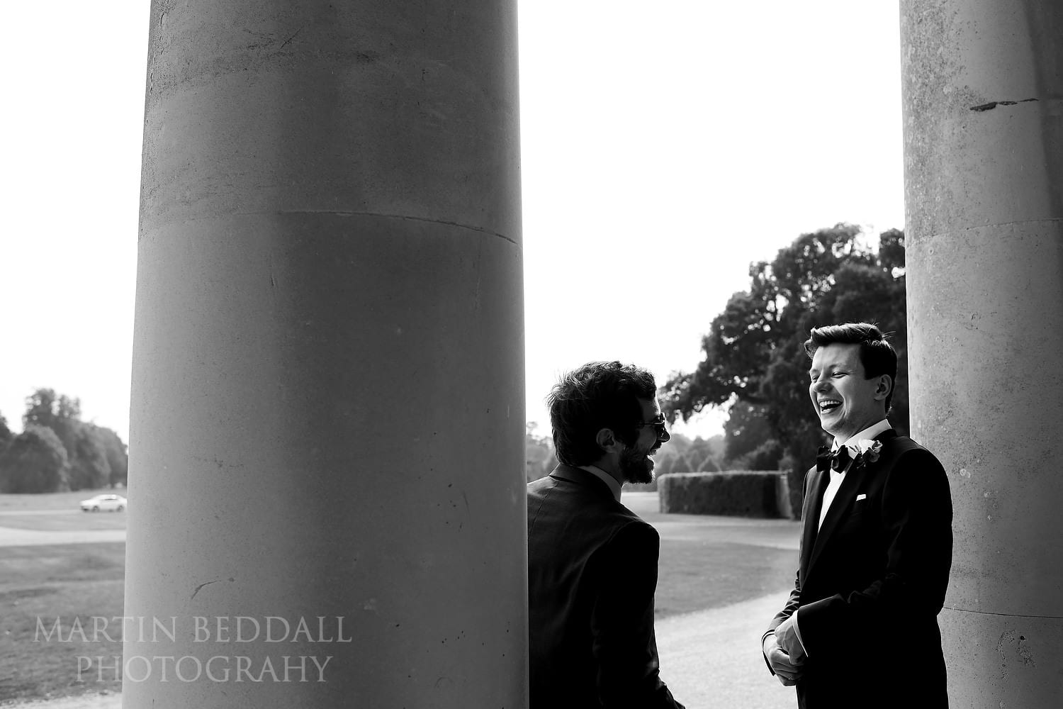 Groom laughing on the steps of Goodwood House