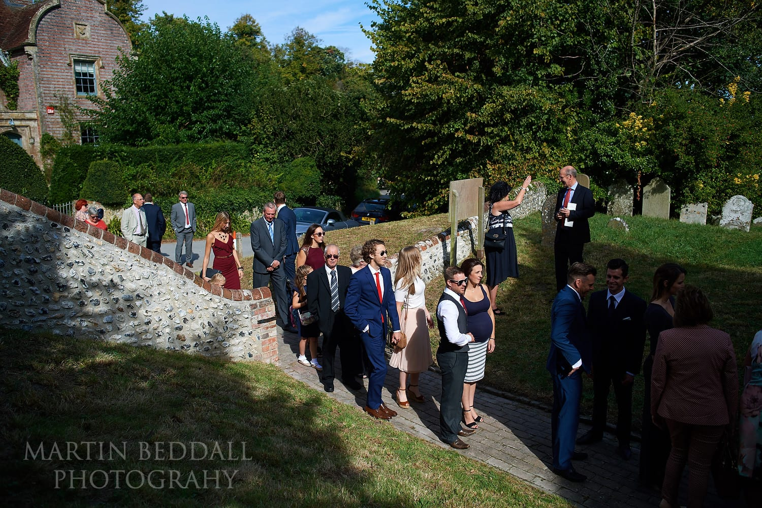 Wedding guests queue to enter the small Church of St Peter ad Vincula at Folkington
