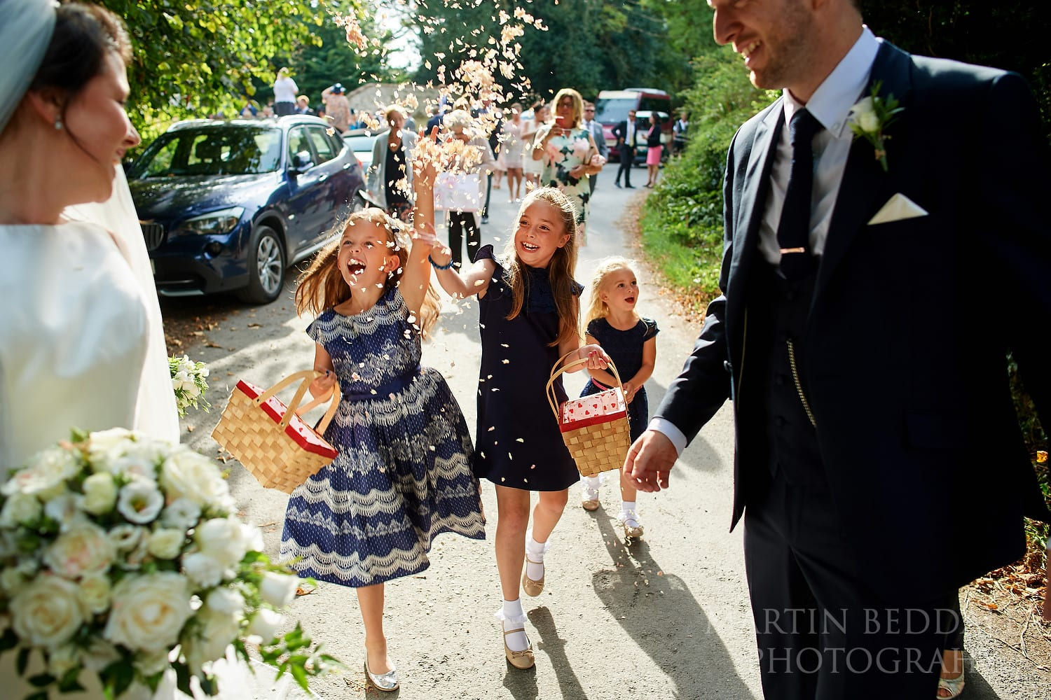 Young girls chase the bride and groom with more confetti
