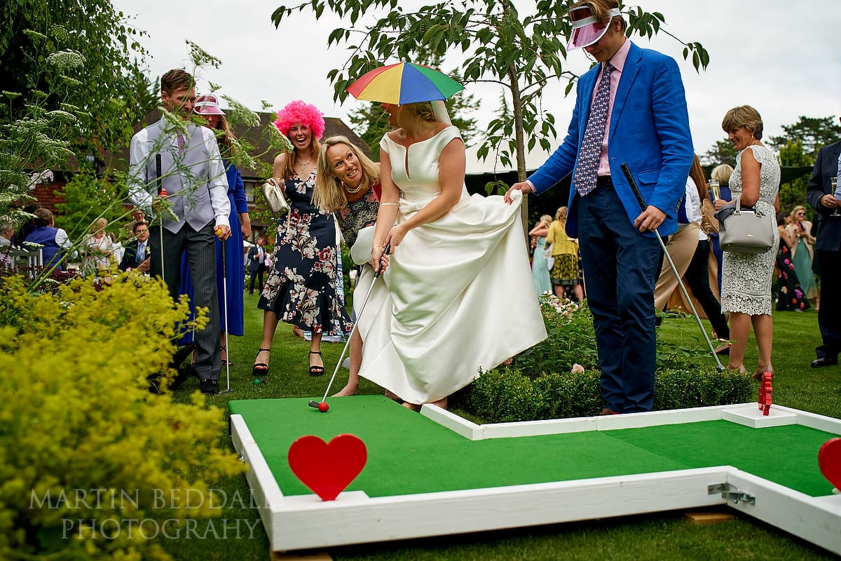 Bride playing mini golf at East Horsley wedding reception