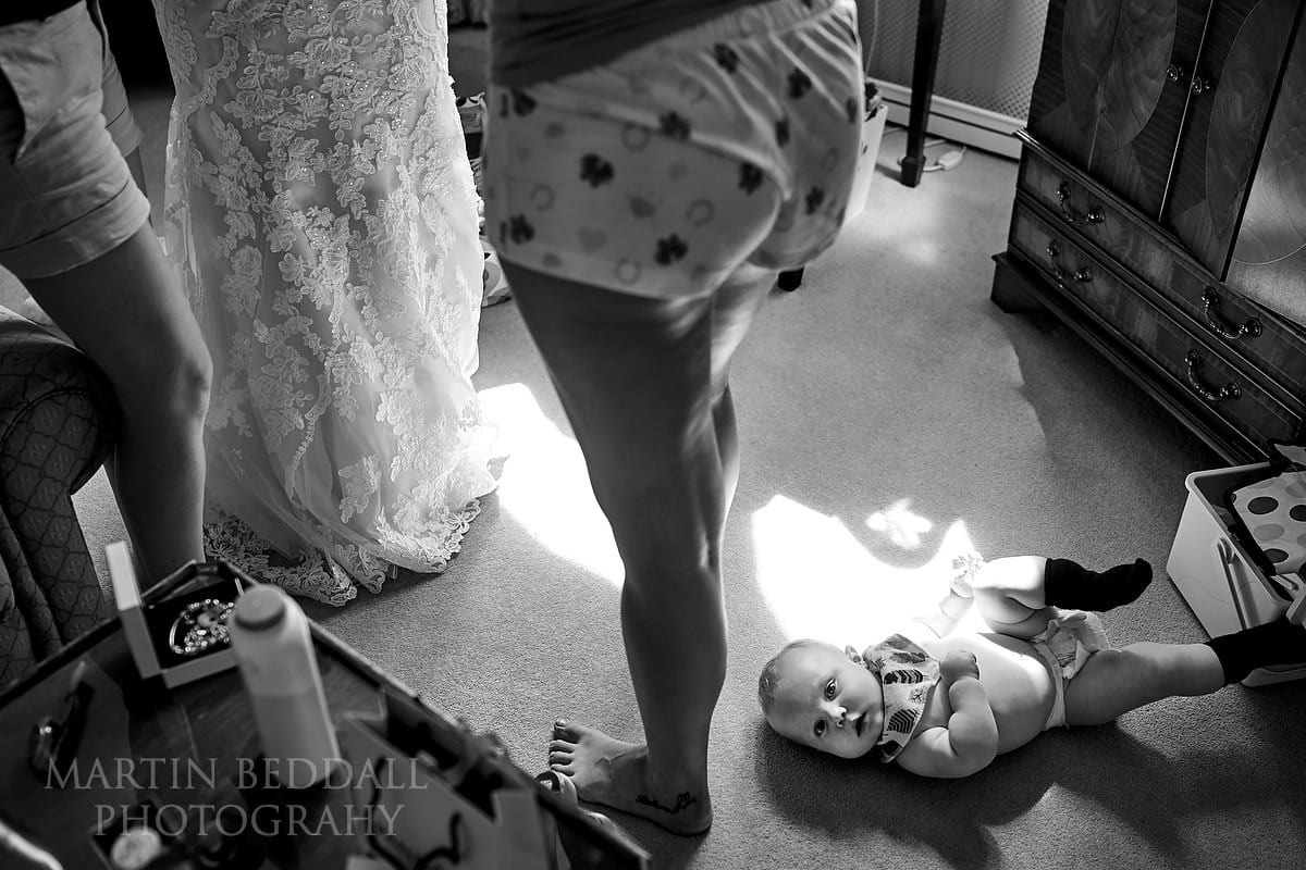 Young son lying on the floor as his mother gets into her wedding dress