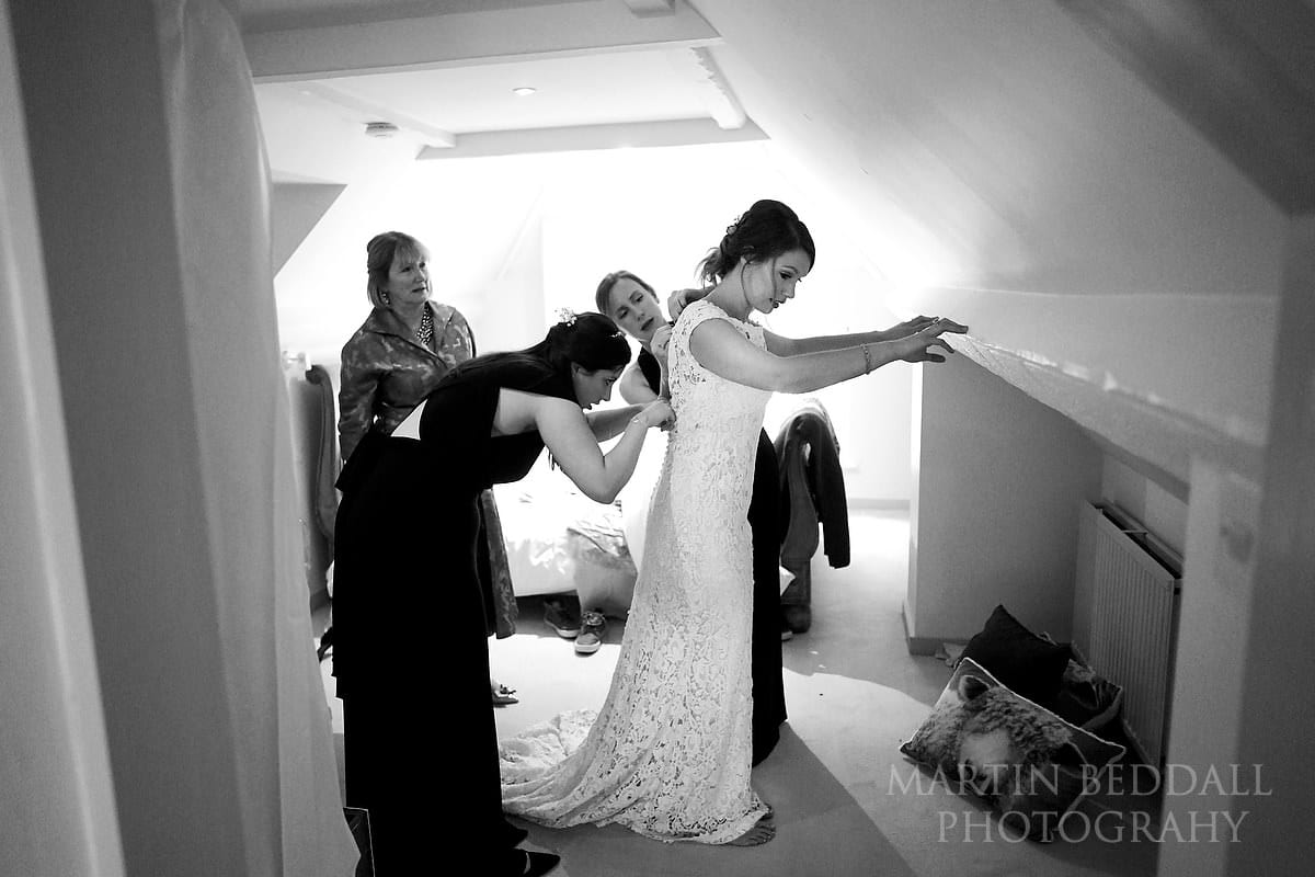 Helping the bride into her wedding dress at The Copse