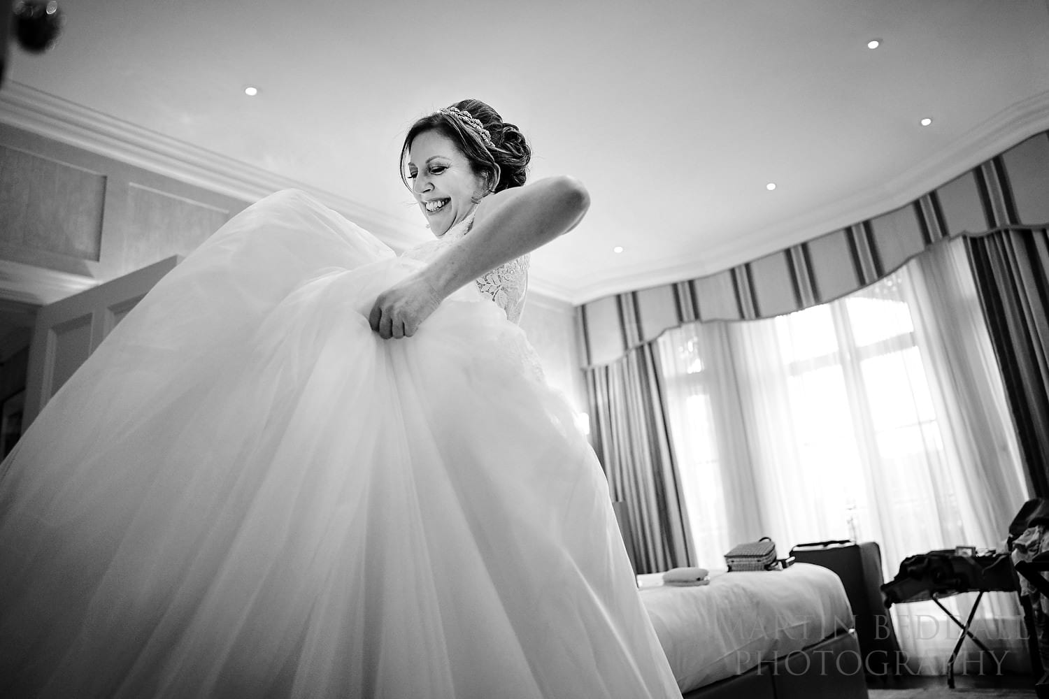 Brider puts on her wedding dress in a room at Claridges