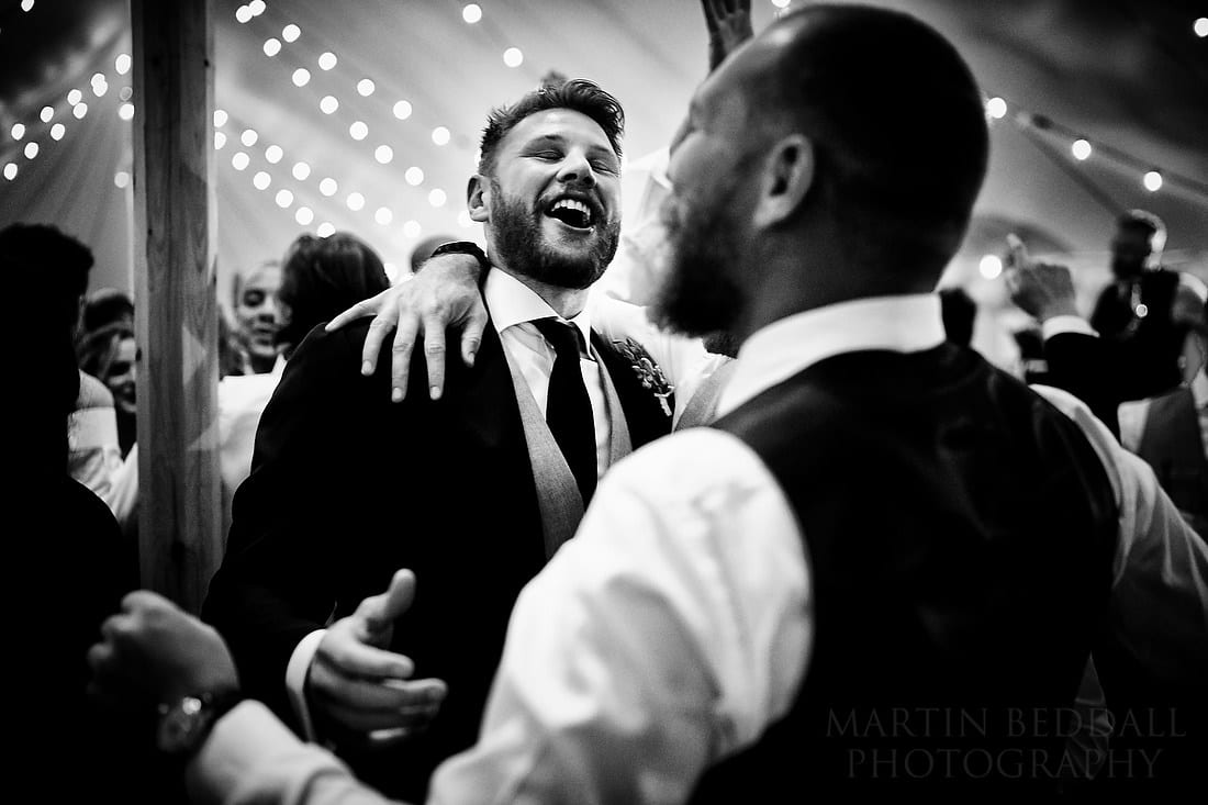 Groom dancing in a marquee at Buckhurst Park