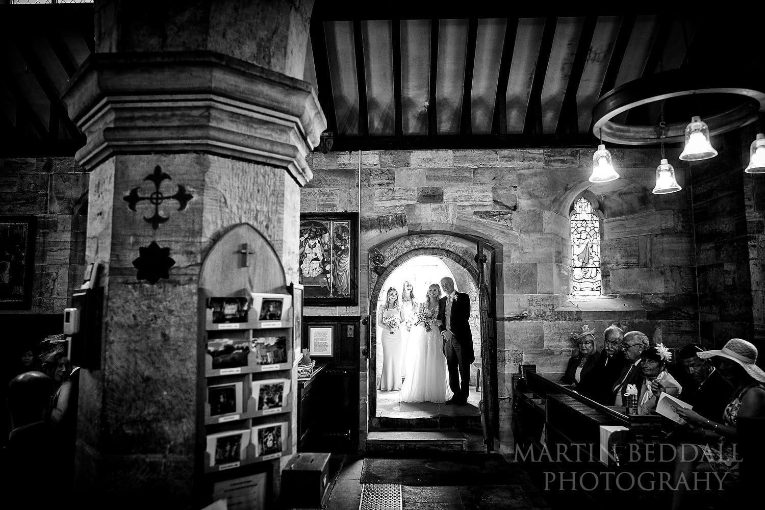 Bride and her father wait to enter St Michael's church in East Sussex
