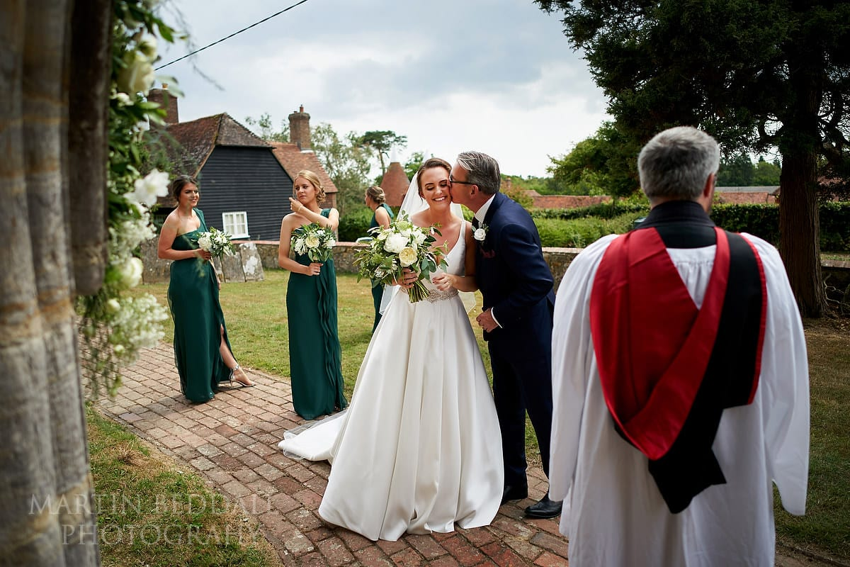 Father of the bride kisses his daughter before they enter the church
