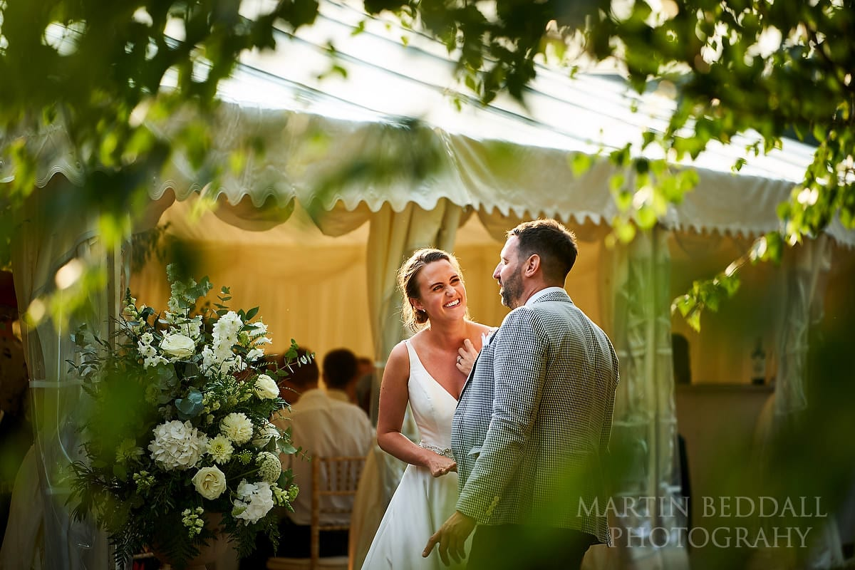 Bride laughing with a guest at Marquee in the garden wedding