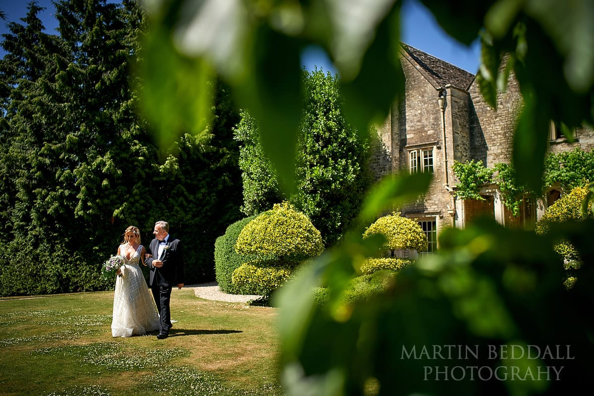Bride escorted across the lawns at Barnsley House by her father