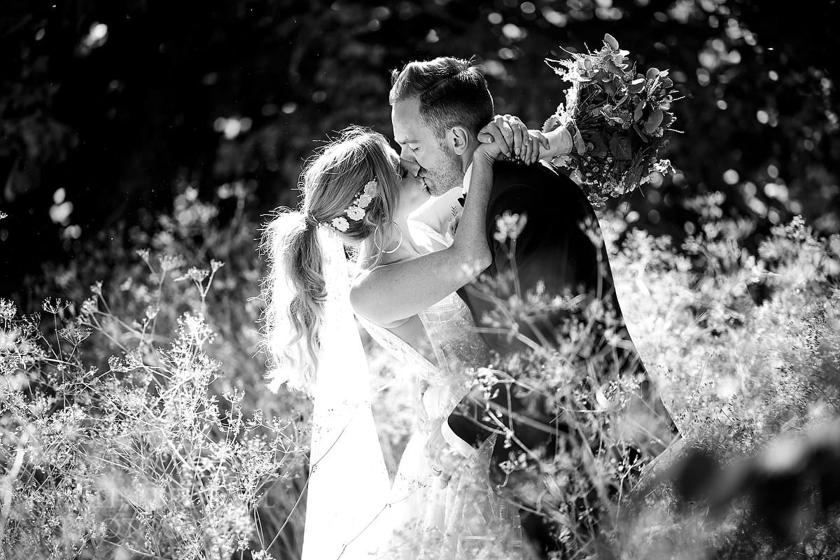 Bride and groom kiss at Barnsley House