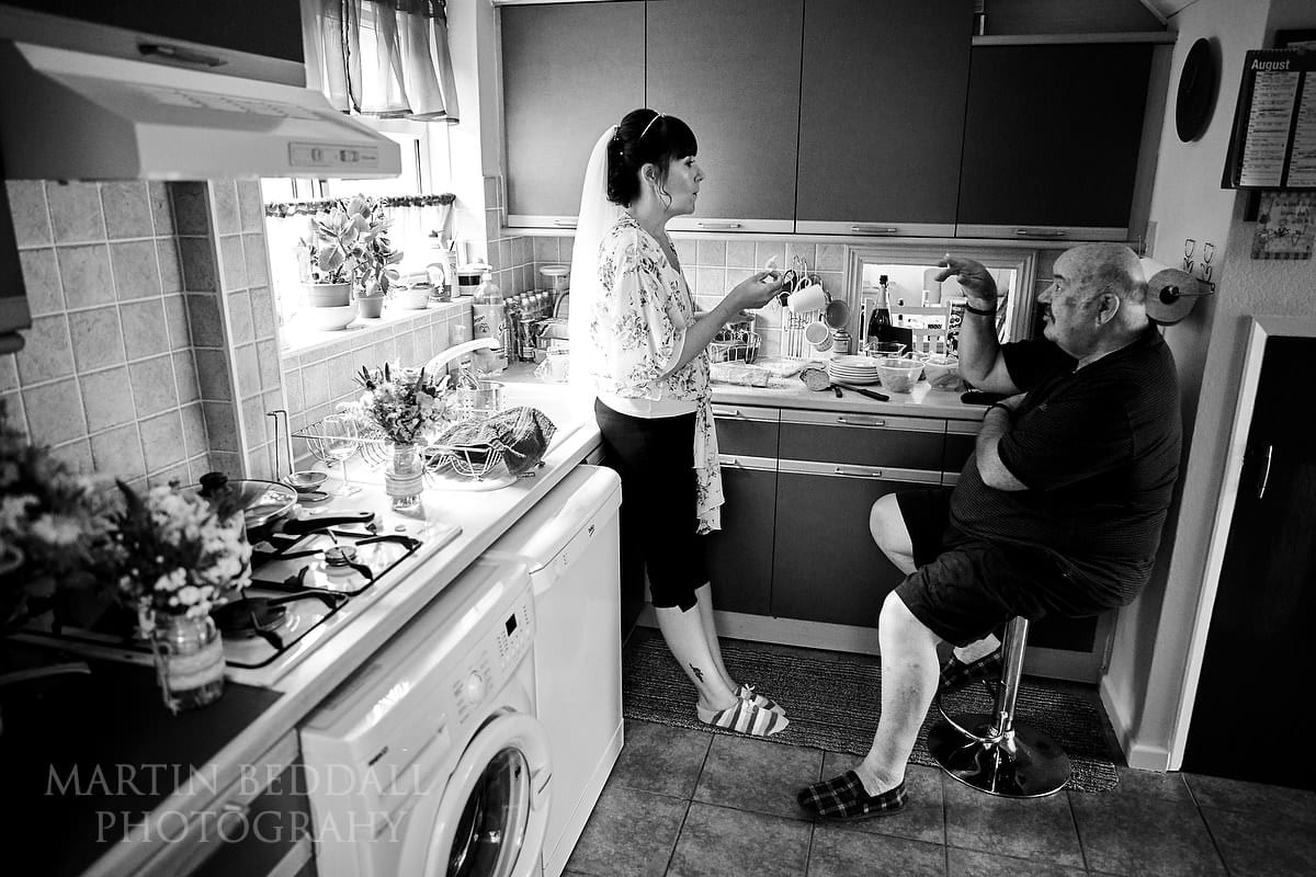 Bride chatting with her father in the kitchen