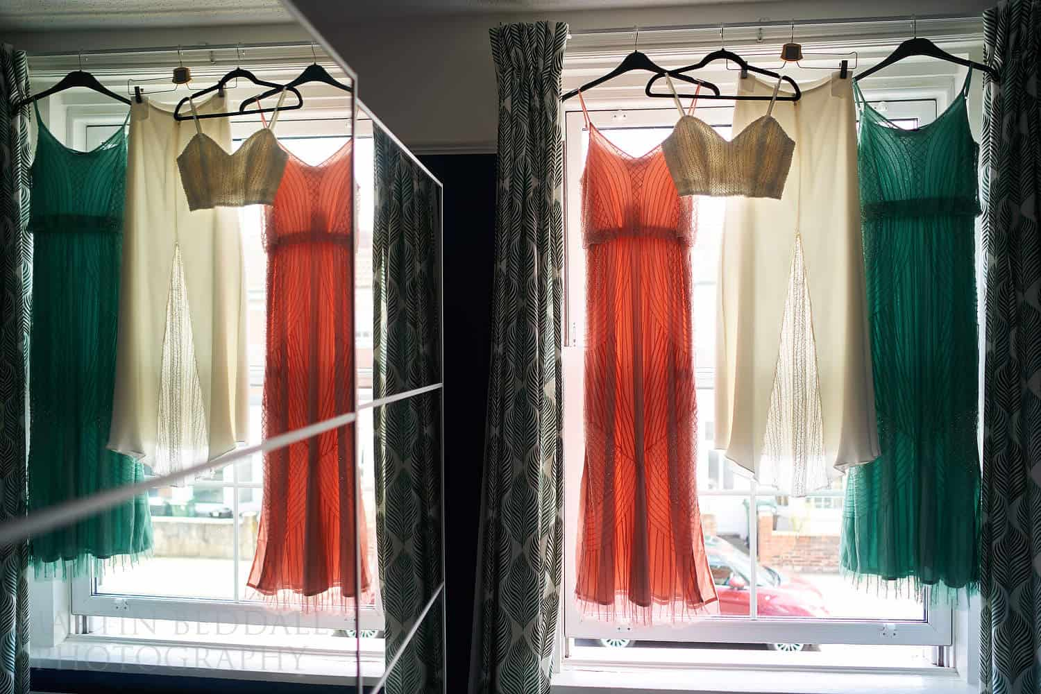Bride and bridesmaids dresses hanging on the window