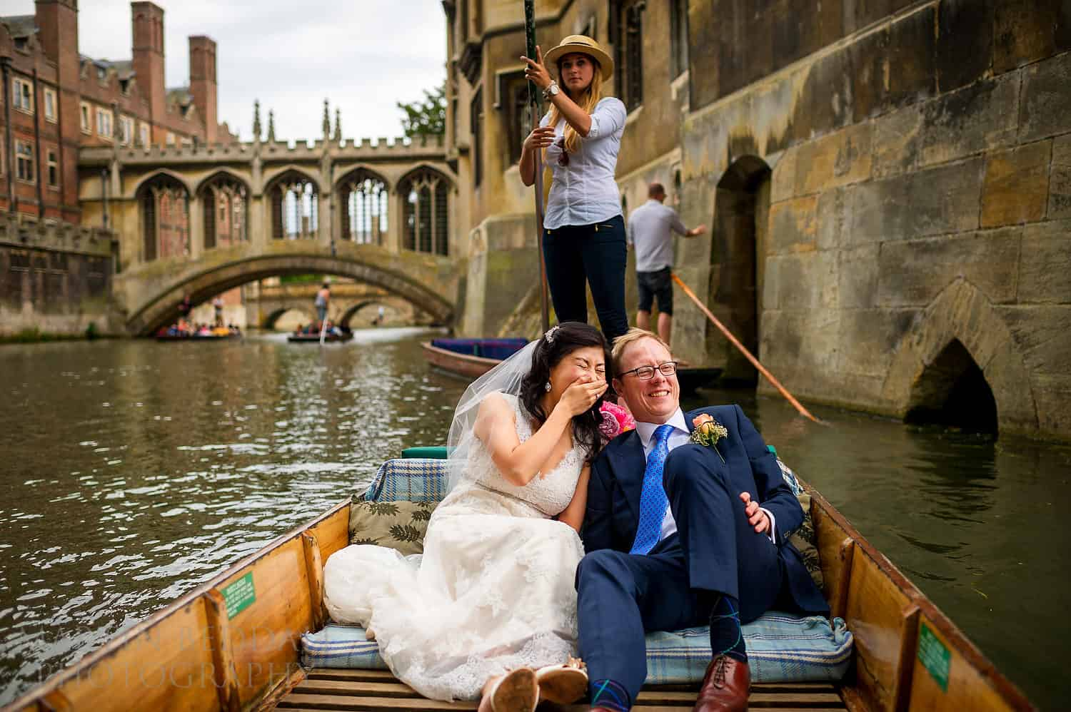 Bride and groom in a punt on the river Cam in Cambridge