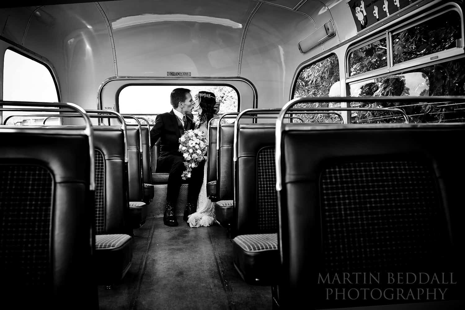 Bride and groom kiss at the back of the bus