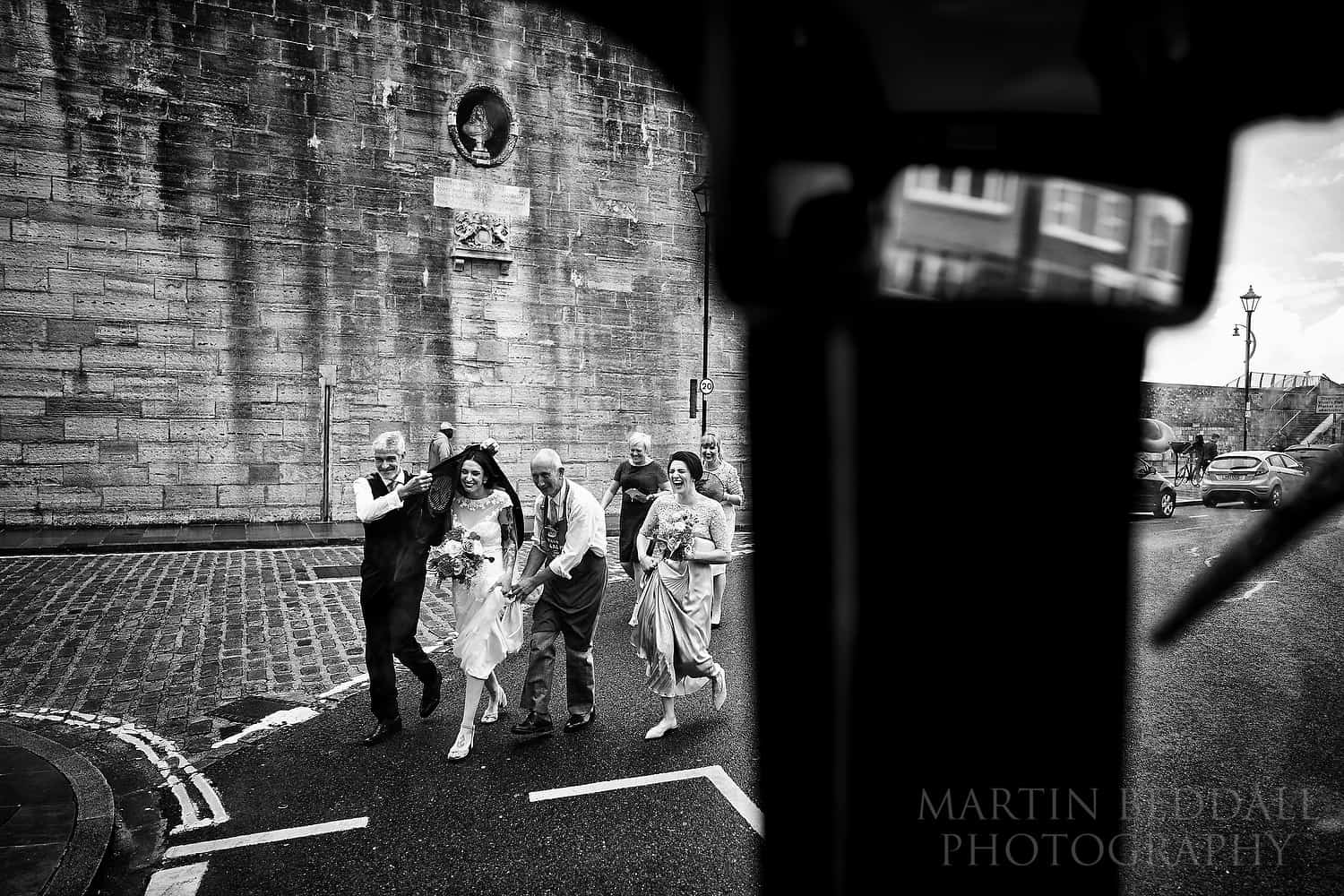Square tower wedding getting to the bus in the rain