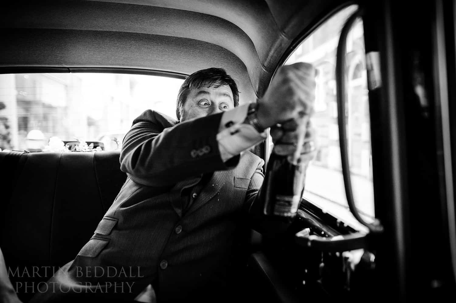 Opening a bottle of champagne in the London taxi