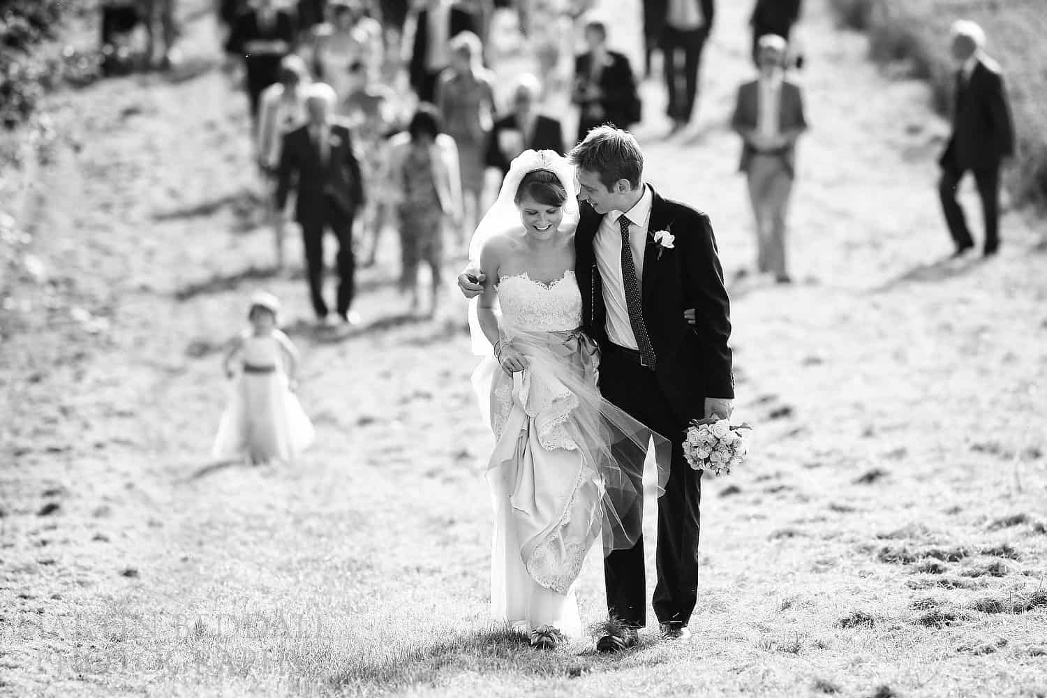 Bride and groom lead the wedding guests across sunny fields to the wedding reception