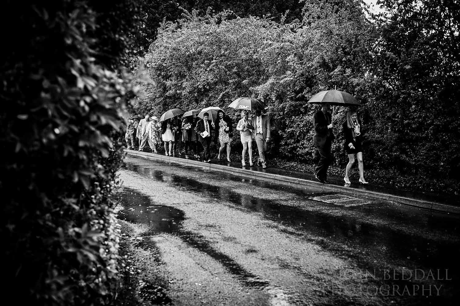 Wedding guests head to the reception in heavy rain