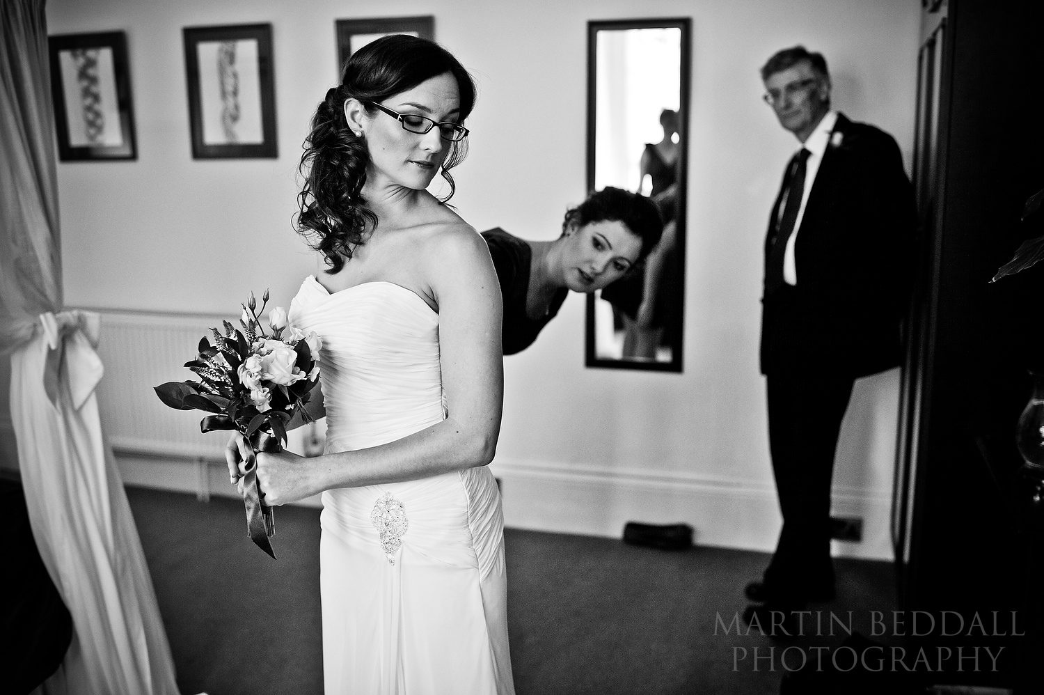 Father looks on as the bride gets ready