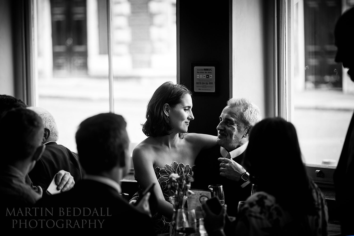 Bride sits on her father's lap