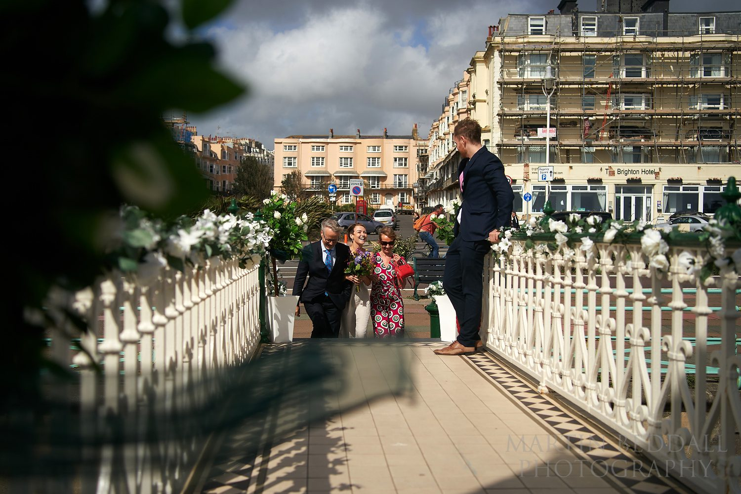 Bride escorted by her father and mother at the bandstand on Brighton seafront