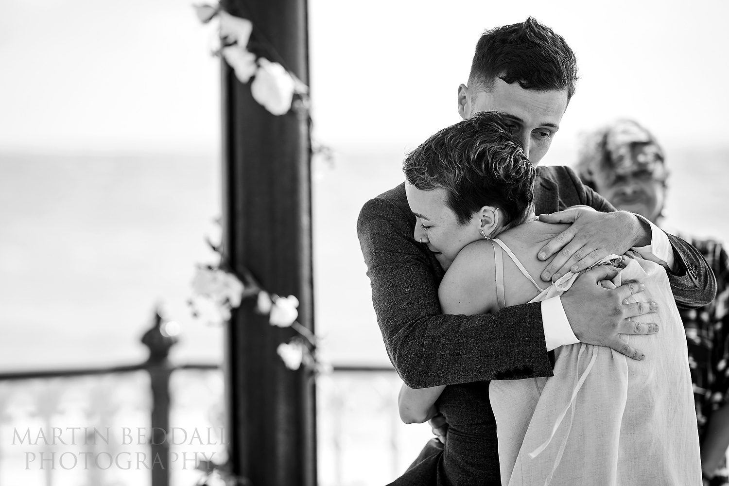 Grooms hugs the bride after her vows