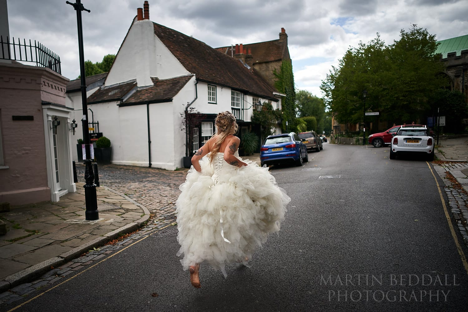 Barefoot bride running to the church in Chiswick